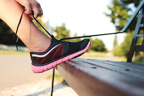 Image of girl tying a running shoe for Girls on the Run Program